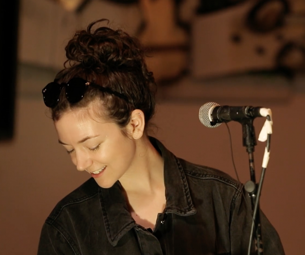 Shannon Sankey wears a black denim jacket and looks down behind a microphone