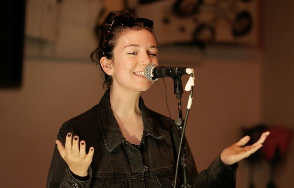 Shannon Sankey wears a black denim jacket and gestures behind a microphone